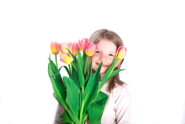 Piękna dziewczyna trzyma bukiet kolorowych kwiatów tulipanów na jasnej powierzchni. 8 marca lub dzień womans. dzień matki. świąteczna koncepcja pozdrowienia.