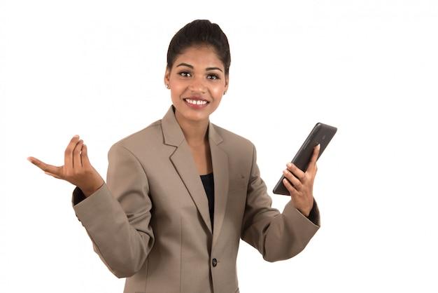 Piękna dziewczyna trzyma coś w ręce z mądrze telefonem lub pastylką i przedstawia