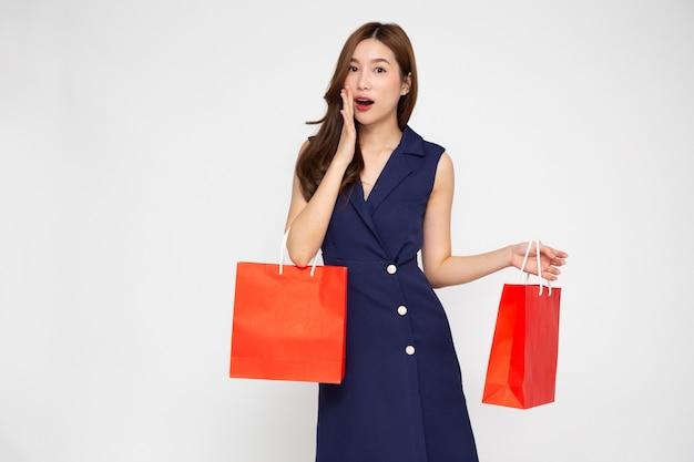 Piękna dziewczyna trzyma czerwone torby na zakupy odizolowane na białym tle