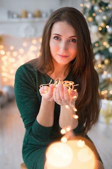 Piękna dziewczyna trzyma girlandę. wystrój noworoczny