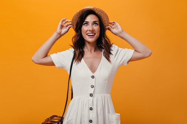 Piękna dziewczyna trzyma kapelusz i uśmiecha się na pomarańczowym tle. urocza kobieta z krótkimi ciemnymi włosami w białej sukni, pozowanie i uśmiechnięta.