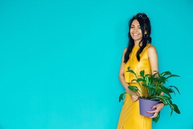 Piękna dziewczyna trzyma kwiat w doniczce na niebieskim tle kobieta trzyma rośliny doniczkowe
