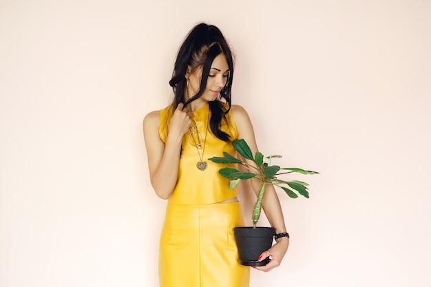 Piękna dziewczyna trzyma kwiat w doniczce na różowym tle kobieta trzyma rośliny doniczkowe