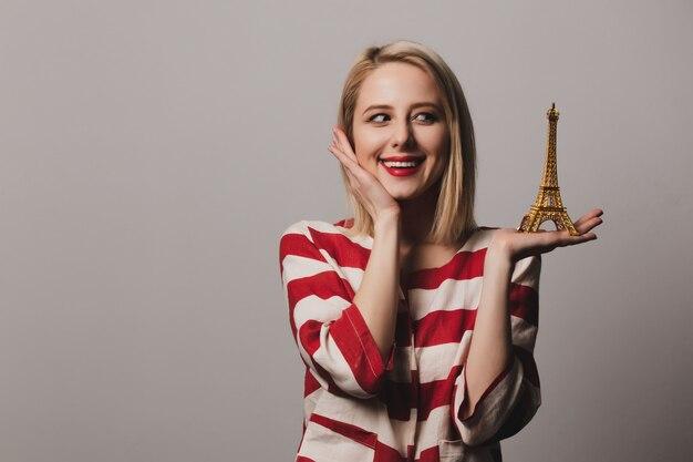 Piękna dziewczyna trzyma pamiątkę ze złotej wieży eiffla