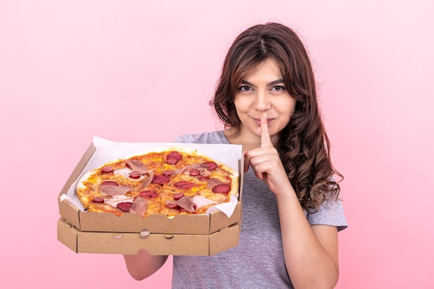 Piękna dziewczyna trzyma pizzę w pudełku do dostawy na różowym tle