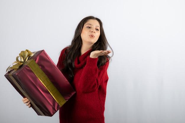 Piękna dziewczyna trzyma prezent gwiazdkowy i dmuchanie pocałunek powietrza.