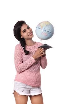 Piękna dziewczyna trzyma światową kulę ziemską odizolowywająca na białej przestrzeni