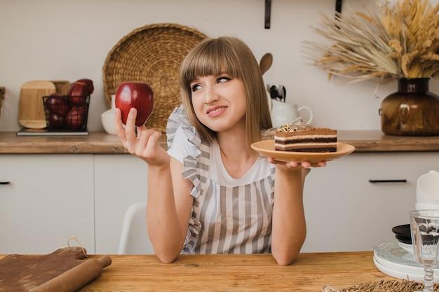 Piękna dziewczyna trzyma w jednej ręce ciasto, a w drugiej jabłko i zastanawia się, co zjeść