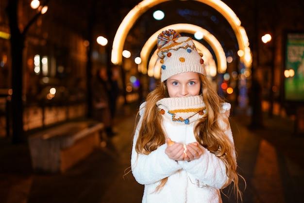 Piękna dziewczyna trzyma w ręku girlandę wieczorem na ulicy w zimie