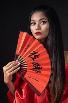 Piękna dziewczyna ubrana jak gejsza w czerwonym kimonie z wachlarzem
