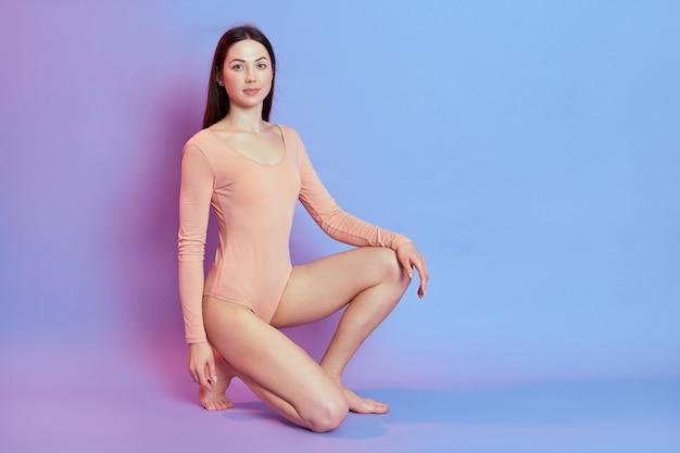 Piękna dziewczyna ubrana w beżowe body z ciemnymi włosami, ma idealne ciało, siedzi na kolanach z pewnym siebie wyrazem, odizolowana na niebieskiej ścianie z różowym neonem.