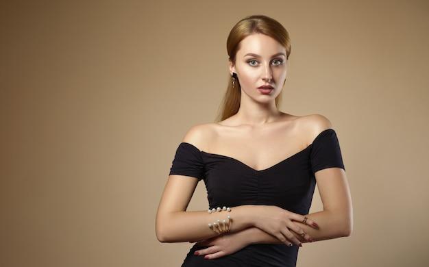 Piękna dziewczyna ubrana w czarną sukienkę na ramionach i perłową złotą bransoletę na beżowej ścianie