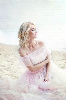Piękna dziewczyna ubrana w długą suknię boho siedzi na plaży. samotna dama siedzi sama na plaży. podróże i wypoczynek. koncepcja wolności. dziewczyna lubi wypoczywać. dziewczyna z blond włosami w różowej sukience. panna młoda
