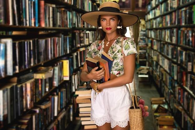 Piękna dziewczyna ubrana w stylowy strój szuka ciekawej książki w małej księgarni vintage