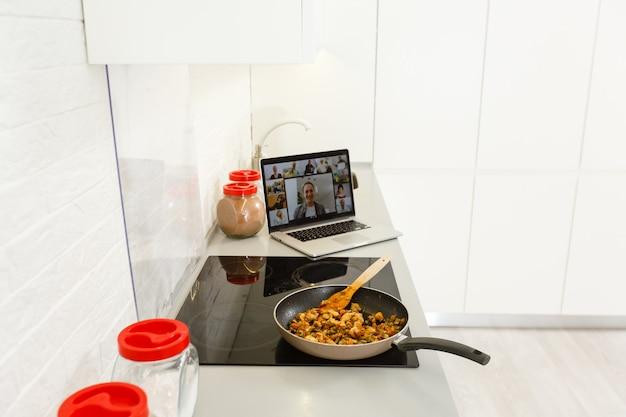 Piękna dziewczyna uczy się gotować zdrową żywność online przez internet z laptopa w szarej kuchni na stole.