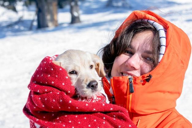 Piękna dziewczyna uśmiecha się i ogrzewa swojego szczeniaka w zimowym mrozie