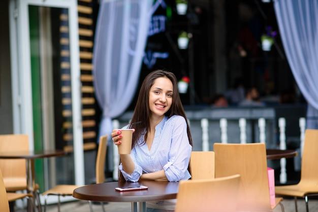 Piękna dziewczyna uśmiecha się i pije kawę.