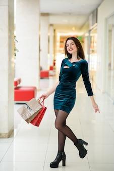 Piękna dziewczyna uśmiecha się i robi zakupy w centrum handlowym.