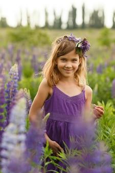 Piękna dziewczyna uśmiecha się w fioletowej sukience z wieńcem łubinów