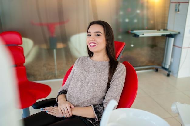 Piękna dziewczyna uśmiecha się w fotelu dentystycznym.