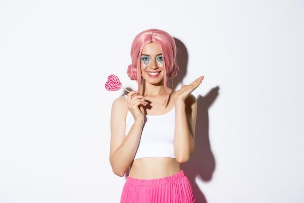 Piękna dziewczyna uśmiechnięta, ubrana w różową perukę i kostium wróżki, trzymając cukierki w kształcie serca, stojąc.