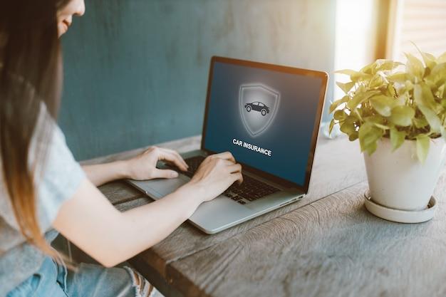 Piękna dziewczyna używa laptop dla szukać ubezpieczenie samochodu online w domu.