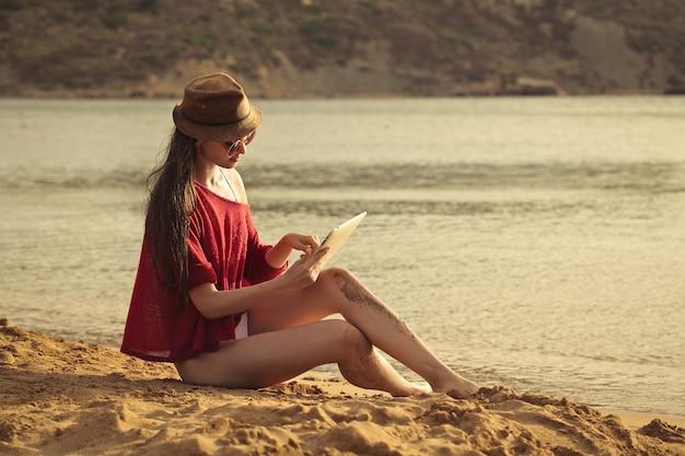 Piękna dziewczyna używa pastylkę na plaży