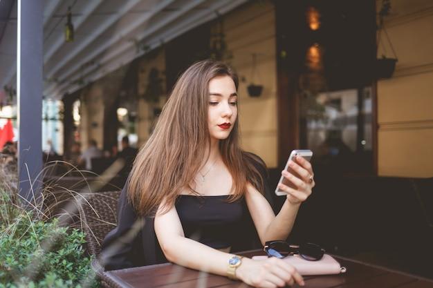 Piękna dziewczyna używa smartfona do komunikowania się w sieci. portret pięknej kobiety z telefonem