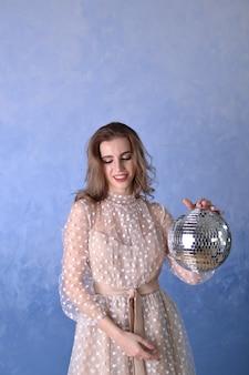 Piękna Dziewczyna W Beżowej Sukience Trzyma W Dłoniach Błyszczącą Kulę Dyskotekową Na Niebieskim Tle Premium Zdjęcia
