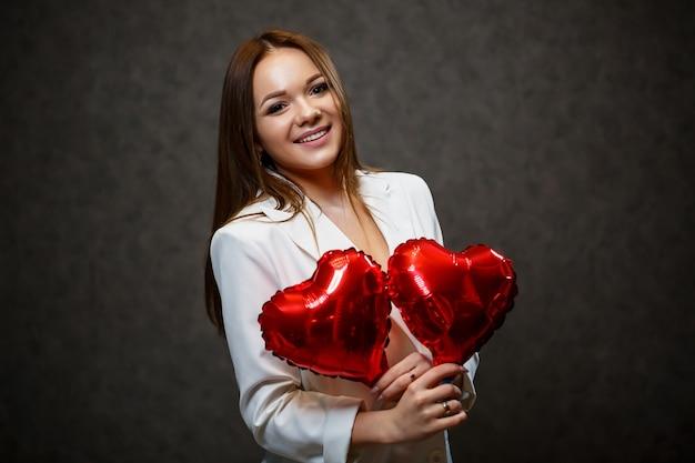 Piękna dziewczyna w białej kurtce z czerwonym balonowym sercem w dłoniach