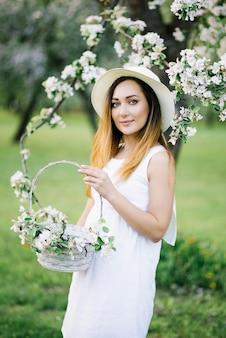 Piękna dziewczyna w białej sukni i białym kapeluszu z rondem trzymająca kosz z gałęziami kwitnącej jabłoni stoi w wiosennym ogrodzie