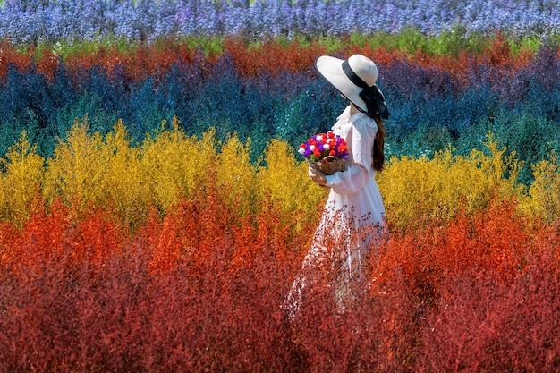 Piękna dziewczyna w białej sukni siedzi na polach tęczowych kwiatów cutter w chiang mai