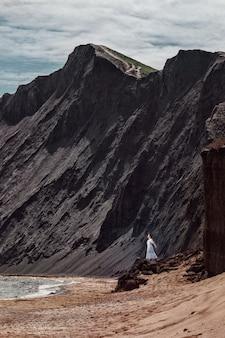 Piękna dziewczyna w białej sukni stoi na klifie