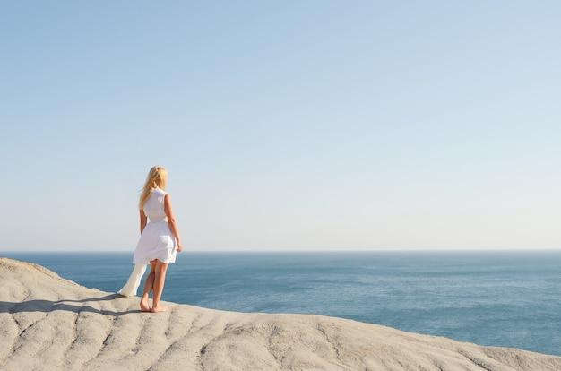 Piękna dziewczyna w białej sukni stojącej na skale i patrząc na morze