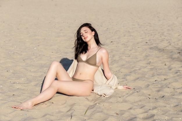 Piękna dziewczyna w białym stroju kąpielowym na plaży. moda piękny portret opalonej kobiety na plaży