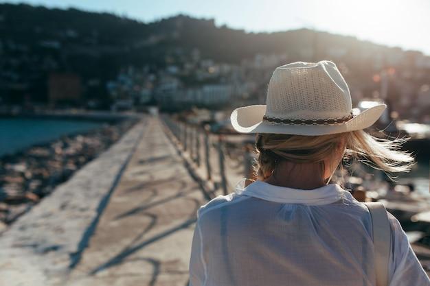 Piękna dziewczyna w bieli spaceruje aleją portu w turcji