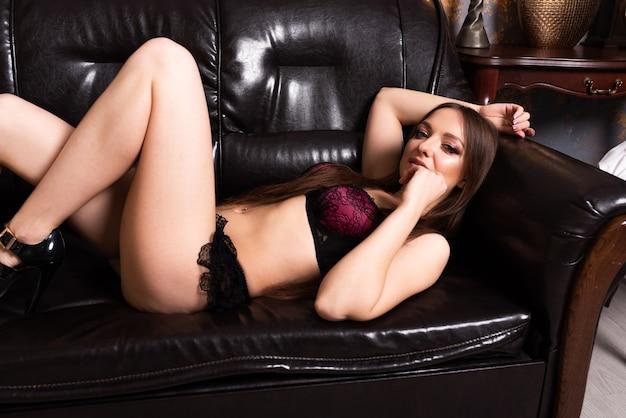 Piękna dziewczyna w bieliźnie leży w uwodzicielskiej pozie na czarnej skórzanej sofie. w dowolnym celu.