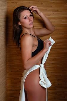 Piękna dziewczyna w bieliźnie w pobliżu bambusowej ściany.