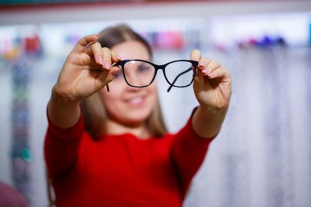 Piękna dziewczyna w centrum okulistycznym podnosi okulary do korekcji wzroku