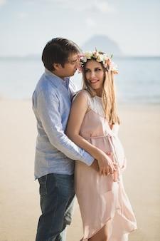 Piękna dziewczyna w ciąży i mężczyzna na plaży