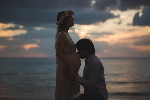 Piękna dziewczyna w ciąży i mężczyzna o zachodzie słońca