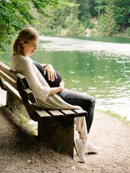 Piękna dziewczyna w ciąży siedzi na ławce nad górskim jeziorem w lesie