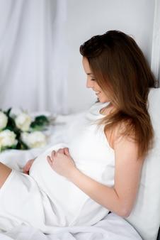 Piękna dziewczyna w ciąży siedzi na łóżku i uśmiecha się.
