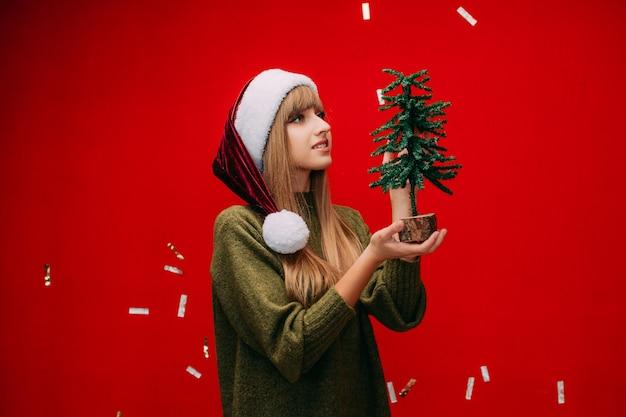 Piękna dziewczyna w czapce mikołaja trzyma w rękach małą choinkę na czerwonym tle