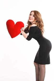 Piękna dziewczyna w czarnej sukience z czerwonym sercem na białym tle pozuje do aparatu w studio, walentynki, makijaż moda luksusowy, czerwone usta. walentynki.