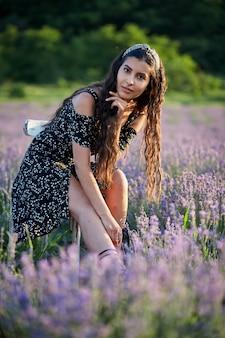 Piękna dziewczyna w czarnej sukni siedzi na drewnianym krześle i pozuje na środku lawendowego pola.