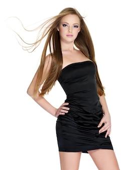 Piękna dziewczyna w czarnej sukni z długimi prostymi włosami na białym tle