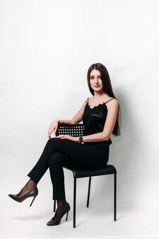 Piękna dziewczyna w czarnych ubraniach siedzi na czarnym krześle na białej ścianie na białym tle