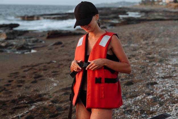 Piękna dziewczyna w czarnym stroju kąpielowym nosi kamizelkę ratunkową na plaży