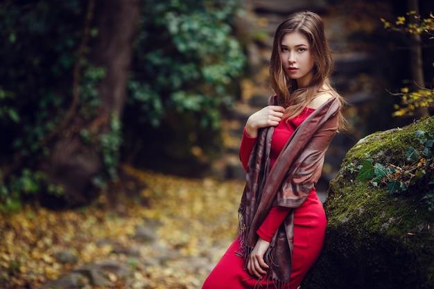 Piękna dziewczyna w czerwonej sukience, długich ciemnych włosach io azjatyckim wyglądzie spaceruje po wiosennym parku